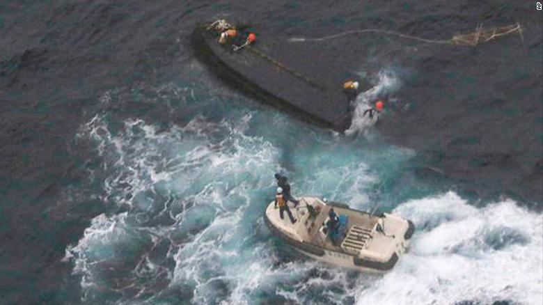 A Japan Coast Guard boat approaches a capsized wooden vessel, on Wednesday, Nov. 15, 2017. Three crew members rescued from the capsized boat are North Koreans, and Tokyo is arranging their return home.