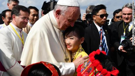 TOPSHOT - Pope Francis is greeted by children in traditional clothing upon his arrival at Yangon International Airport on November 27, 2017. Pope Francis arrived in Myanmar on November 27 at the start of a highly sensitive four-day trip to a country facing global condemnation over its treatment of Rohingya Muslims. / AFP PHOTO / Vincenzo PINTO        (Photo credit should read VINCENZO PINTO/AFP/Getty Images)