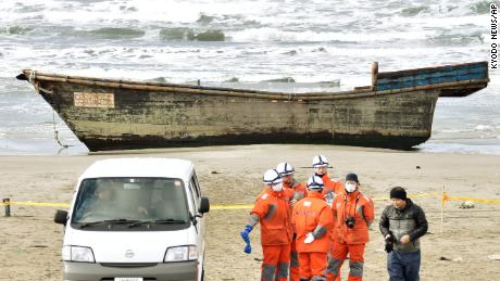 Japanese officials gather on Nov. 27, 2017, near a boat washed ashore in Oga, Akita Prefecture. Authorities found eight bodies in the unidentified wooden boat. (Kyodo) ==Kyodo