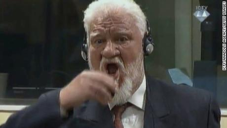 Crotian Former General Slobodan Praljak drinking a small bottle of liquid during a Yugoslav War Crimes Tribunal in The Hague on November 29.