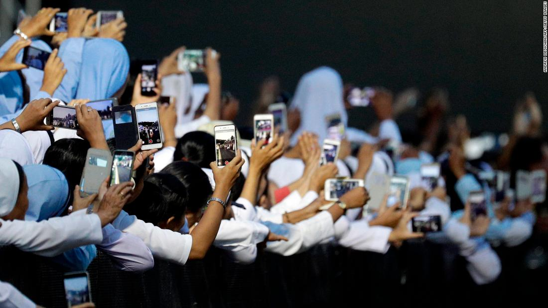 Nuns hold their phones to film the Pope as he arrives for a meeting in Yangon on November 29.
