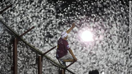 A Lanus fan cheers his team on before kick off.