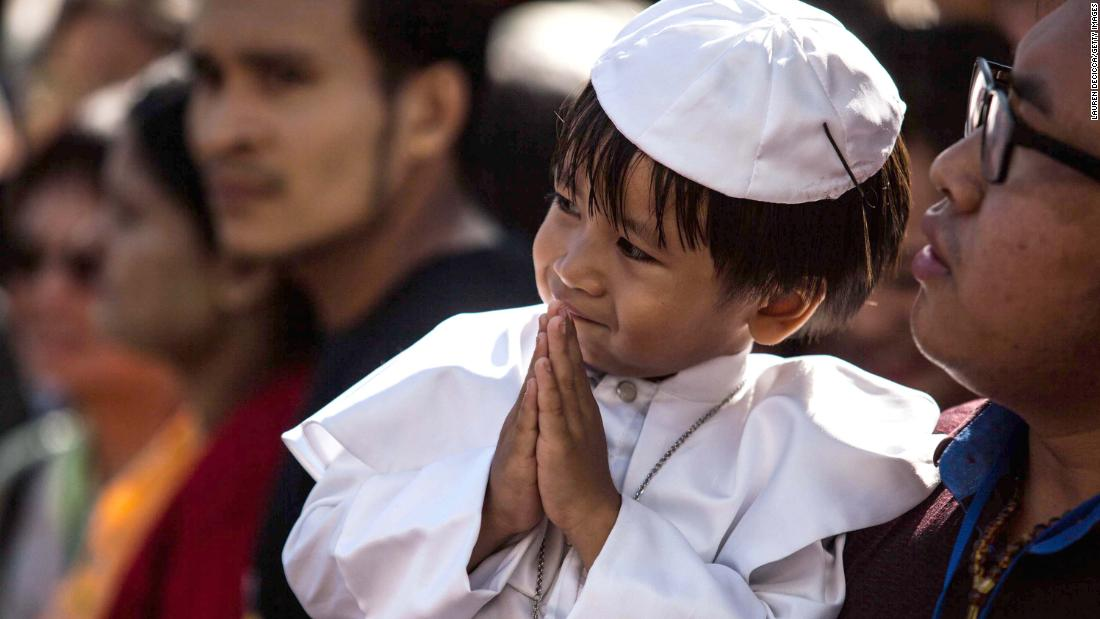 A young boy in a miniature Pope outfit is seen waiting outside St. Mary's Catholic Church in Yangon, awaiting Pope Francis' arrival November 30.