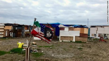 "A US flag bearing Jim Morisson's face flies next to an Italian flag, amid the makeshit homes of the ""Runway Ghetto,"" in Foggia."