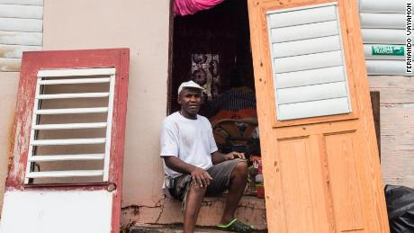A man waits to replace his damaged door in Christiansted, a day after Maria hit.
