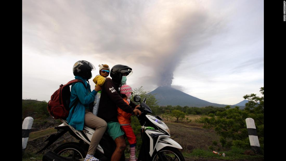 "Mount Agung erupts in the background as a family rides on a motorcycle in Karangasem, Indonesia, on Monday, November 27. <a href=""http://www.cnn.com/2017/11/26/asia/mount-agung-eruption-bali-indonesia/index.html"" target=""_blank"">The volcanic eruptions</a> from Mount Agung, on the resort island of Bali, forced the closure of the island's main airport and the evacuation of thousands of residents living nearby."