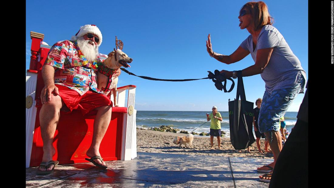 Carol Kelley tries to get the attention of her dog, Kaylee, as Kaylee sits for a photo with Santa Claus in Jupiter, Florida, on Tuesday, November 28.