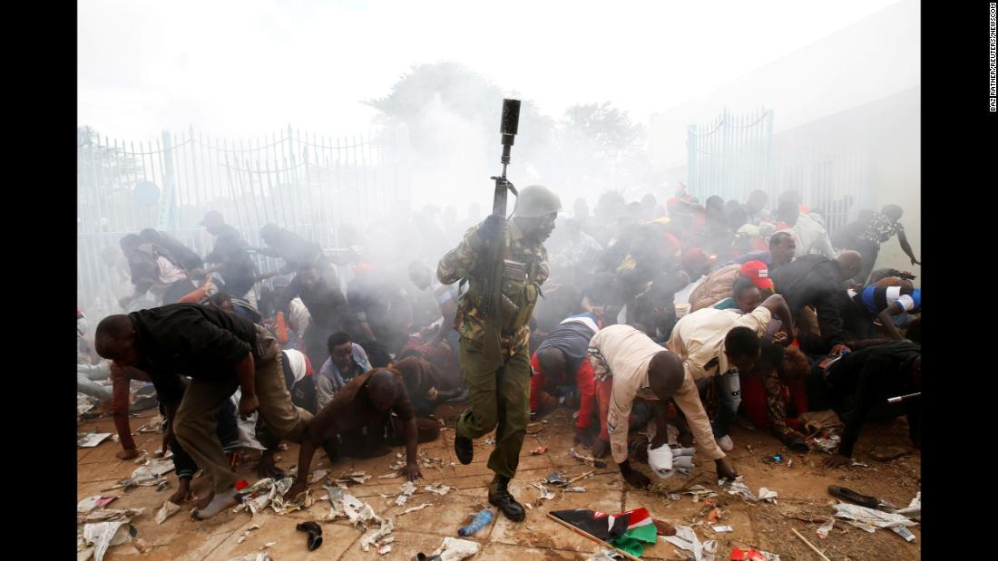 People fall in Nairobi, Kenya, as police fire tear gas to control a crowd trying to force their way into a stadium to attend the inauguration of President Uhuru Kenyatta on Tuesday, November 28.