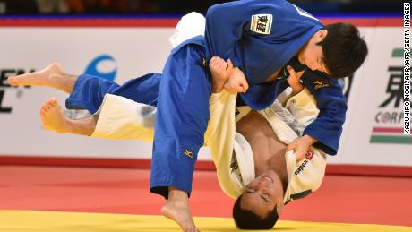 Japan's Toru Shishime (L) throws down Brazil's Felipe Kitadai (R) in the men's 60-kilogram category bronze medal contest at the Judo Grand Slam Tokyo on December 4, 2015. AFP PHOTO / KAZUHIRO NOGI / AFP / KAZUHIRO NOGI        (Photo credit should read KAZUHIRO NOGI/AFP/Getty Images)