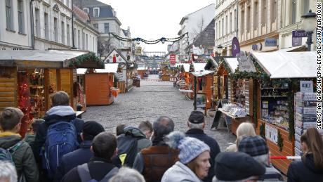 Crowds gather behind a police line after the Potsdam Christmas market was evacuated due to an explosive device on December 1.