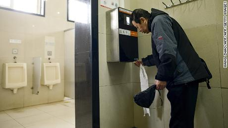 A man uses an automatic toilet paper dispenser that uses facial recognition technology at a public toilet at the Temple of Heaven in Beijing on March 21, 2017. 