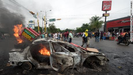A car burns after being set on fire by supporters of Honduran presidential candidate Salvador Nasralla during post-election protests.