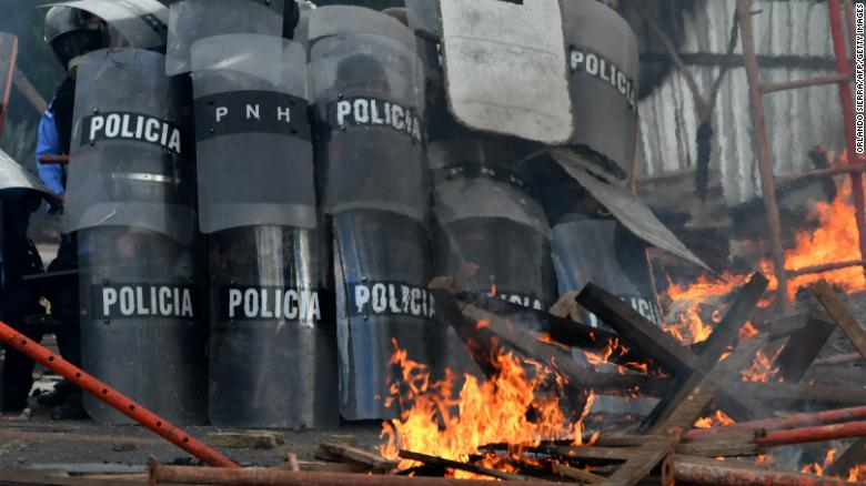 Police officers in riot gear clash with supporters of Honduran presidential candidate Salvador Nasralla in Tegucigalpa as the country waits for the final results of last weekend's presidential election.