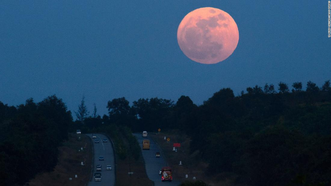 The supermoon rises over a highway near Yangon, Myanmar. The lunar phenomenon occurs when a full moon is at its closest point to Earth.