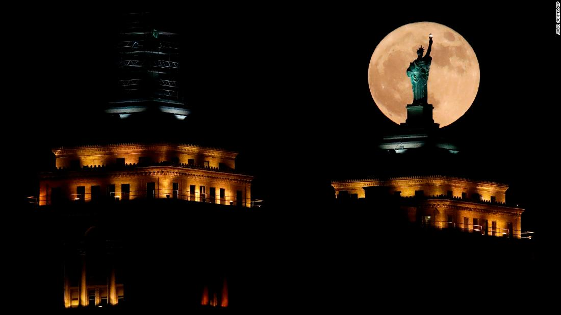 The moon rises in front of a replica of the Statue of Liberty sitting atop the Liberty Building in downtown Buffalo, N.Y.