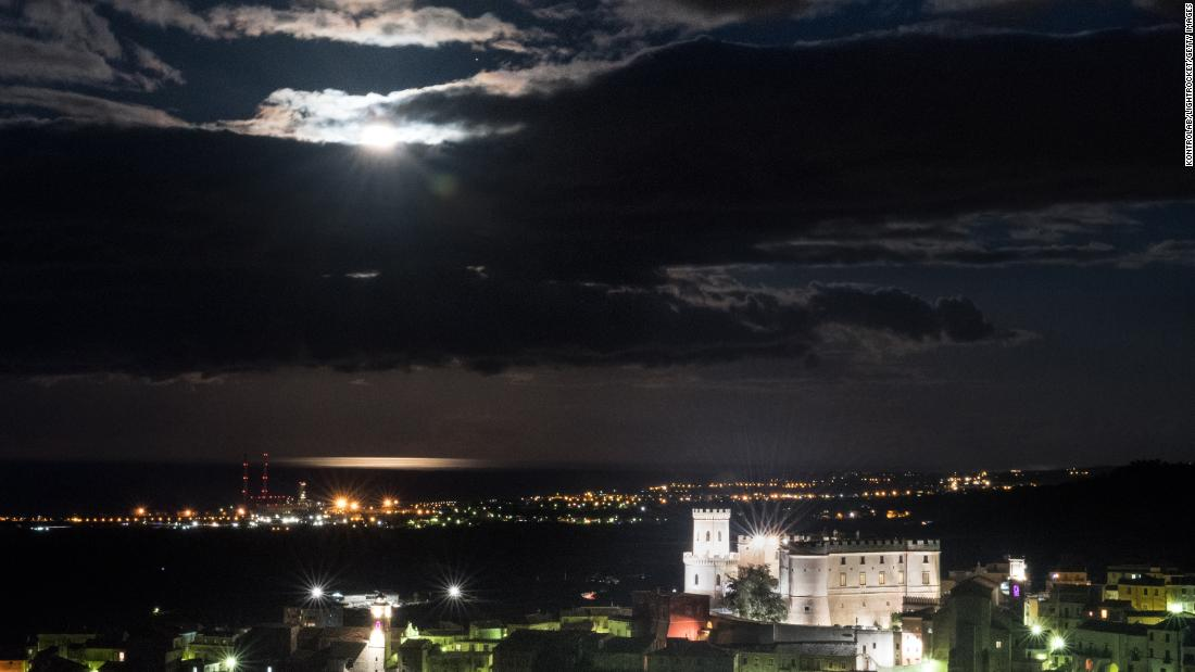 The year's only supermoon is bright behind the clouds above the Castle of Corigliano, in Calabria, southern Italy.