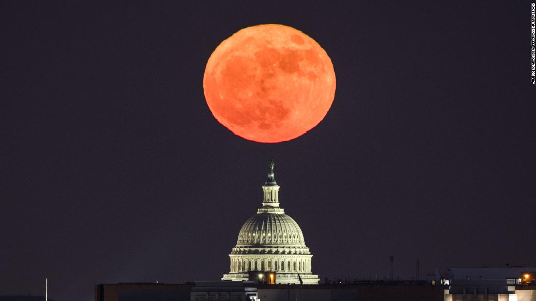 The moon rises behind the US Capitol in Washington, DC, viewed from Arlington, Virginia.