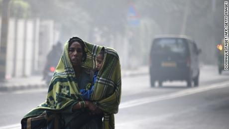 An Indian woman and her child walk amid heavy smog on a street in New Delhi on December 4, 2017.