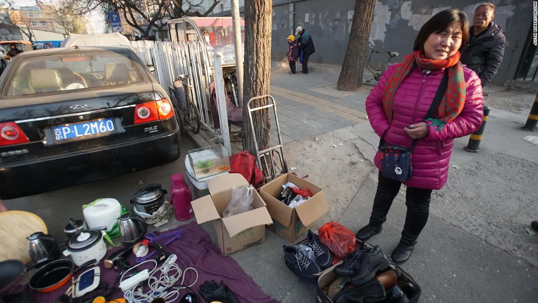 Zhao Guihua, an evicted migrant worker, sells her possessions on the street 50 meters from her old home. She said she and her husband are leaving Beijing because they can't afford a new home.