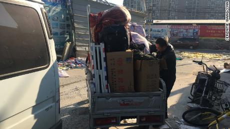 A migrant worker packs his things after being evicted from his rented apartment.