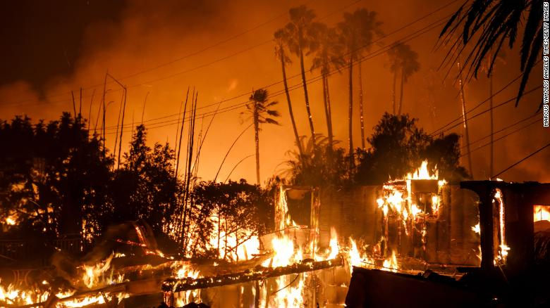 A home is destroyed by a brush fire as Santa Ana Winds help propel the flames to move quickly.
