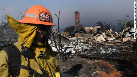 A firefighter looks at a house burnt to the ground during the Thomas wildfire in Ventura, California on December 5, 2017. Fast-moving, wind-fueled brush fire exploded to about 10,000 acres in Ventura County Monday night, forcing hundreds of people to flee their homes, officials said.  / AFP PHOTO / MARK RALSTONMARK RALSTON/AFP/Getty Images