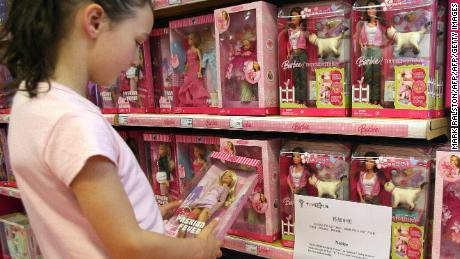 "A young girl holds a Barbie doll next to a notice saying that the toy ""Barbie and Tanner"" made by US toy giant Mattel, which has just been recalled in the US, is out of stock at a Toys ""R"" Us store in Shanghai, 15 August 2007.  The US Consumer Product Safety Commission announced the recall of millions of toys manufactured by Mattel Inc., including the Barbie and Tanner play sets, at the commission's headquarters in Bethesda, Maryland. According to the commission, the play sets' ""scooper"" accessory has a small magnet that can come loose and if more than one magnet is swallowed they can attract each other and cause intestinal perforation or blockage, which can be fatal.        AFP PHOTO/Mark RALSTON (Photo credit should read MARK RALSTON/AFP/Getty Images)"