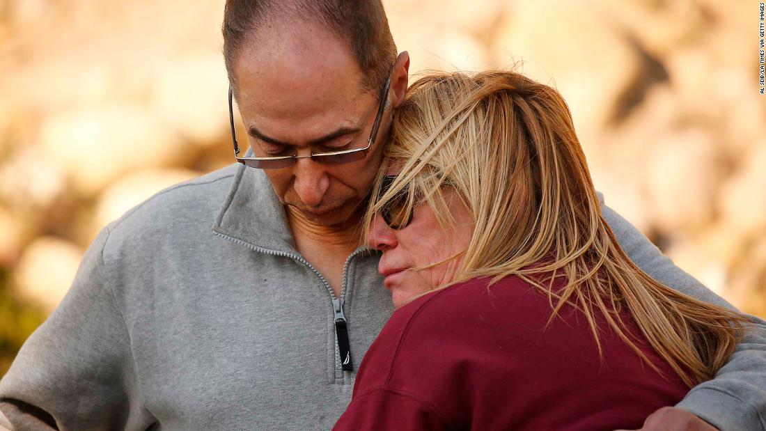 Antoine Hanna comforts his wife, Tammy, after firefighters saved their home in Ventura on December 5.