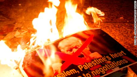 Palestinian demonstrators burn posters of the US president in Bethlehem's Manger Square in protest to him declaring Jerusalem as Israel's capital on December 6, 2017. Abbas said the United States can no longer play the role of peace broker after Donald Trump's decision on Wednesday to recognise Jerusalem as Israel's capital. / AFP PHOTO / Musa AL SHAER