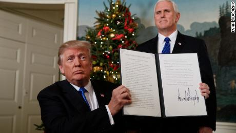 Vice President Mike Pence watches as President Donald Trump holds up a proclamation to officially recognize Jerusalem as the capital of Israel, in the Diplomatic Reception Room of the White House, Wednesday, Dec. 6, 2017, in Washington. (AP Photo/Evan Vucci)