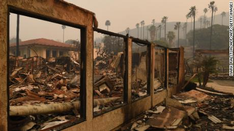 A wall stands in the burnt out Vista del Mar Hospital after the Thomas wildfire swept through Ventura, California on December 6, 2017. California motorists commuted past a blazing inferno Wednesday as wind-whipped wildfires raged across the Los Angeles region, with flames  triggering the closure of a major freeway and mandatory evacuations in an area dotted with mansions. / AFP PHOTO / Mark RALSTON
