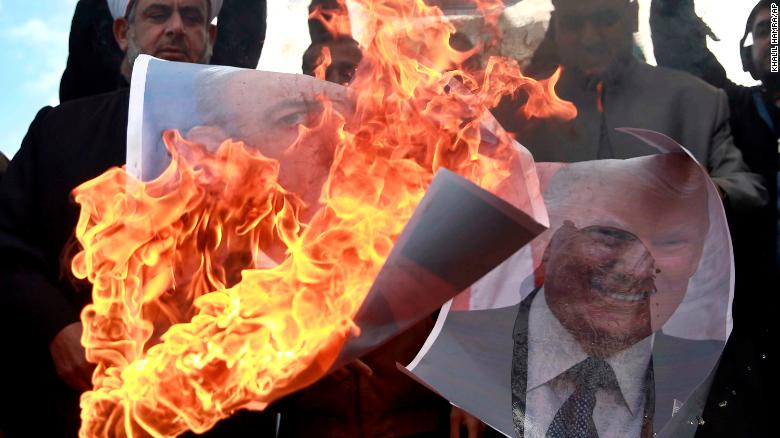 Palestinians burn posters of Israeli Prime Minister Benjamin Netanyahu and US President Donald Trump during a protest Thursday.