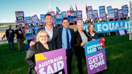 Australian actor Magda Szubanski (far left) and Olympic swimmer Ian Thorpe (second left) seen with equality ambassadors and volunteers outside Parliament House.