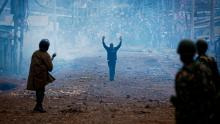 A man seeking safety walks with his hands in the air through a thick cloud of tear gas towards riot police, as they clash with protesters throwing rocks in the Kawangware slum of Nairobi, Kenya Thursday, Aug. 10, 2017. International observers on Thursday urged Kenyans to be patient as they awaited final election results following opposition allegations of vote-rigging, but clashes between police and protesters again erupted in Nairobi. (AP Photo/Ben Curtis)