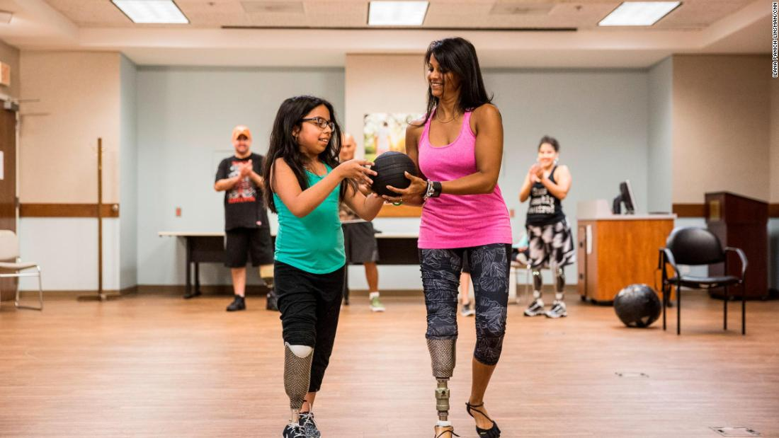 "Patel exercises with Bennelina, whose leg was amputated during a battle with cancer that began at age 7. Patel offered support before Bennelina's surgery and went on to explain the many prosthetic options available to amputees. Bennelina decided on a prosthesis similar to Patel's, making them ""<a href=""http://www.cnn.com/video/data/2.0/video/us/2017/10/05/cnn-heroes-patel-extra.cnn.html"">Sparkle Twins</a>."""