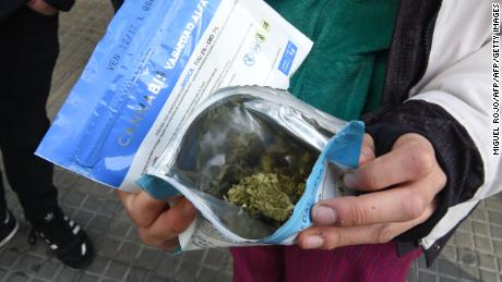 A man shows two envelopes containing marijuana he just purchased at a pharmacy in Montevideo, on July 19, 2017. Pharmacies in Uruguay start selling marijuana from Wednesday under the final phase of a four-year-old law that made the small South American country the first in the world to legalize pot from production to sale. / AFP PHOTO / MIGUEL ROJO        (Photo credit should read MIGUEL ROJO/AFP/Getty Images)
