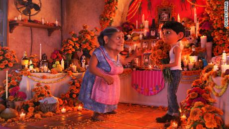 "COCO (Pictured) - DON'T FORGET THE SHOES -- In Disney•Pixar's ""Coco,"" Abuelita (voice of Renée Victor) and Miguel (voice of Anthony Gonzalez) ensure that their home is adorned for Día de Muertos, including an elaborate ofrenda that holds several framed family pictures, flowers, candles, favorite foods and—because they are in the shoemaking business—shoes. ""Coco"" opens in n U.S. theaters on Nov. 22, 2017. ©2017 Disney•Pixar. All Rights Reserved."