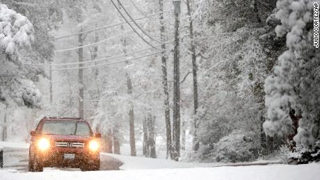 A vehicle drives along Lakeway Drive as snow covers the area following an early morning snowstorm, Friday, Dec. 8, 2017, in Brandon, Miss. The forecast called for a wintry mix of precipitation across several Deep South states. (AP Photo/Julio Cortez)
