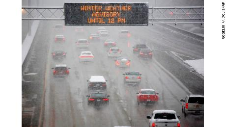 A heavy morning snow falls in Jackson, Miss., Friday, Dec. 8, 2017, as an electronic sign posts a winter weather advisory for drivers along I-55.  The forecast called for a wintry mix of precipitation across several Deep South states.  (AP Photo/Rogelio V. Solis)