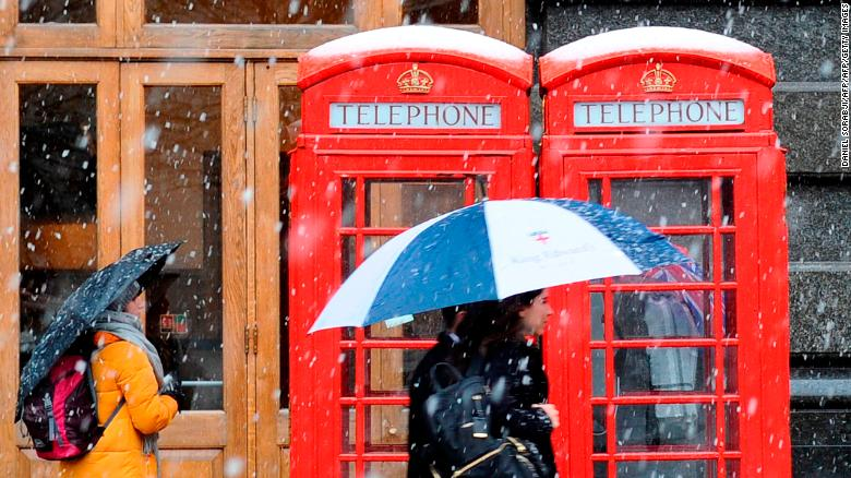 Snow falls on crowds in central London on Sunday.