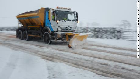 A snow plow clears country lanes in Welsh Frankton, England.