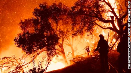Firefighters battle flames as they advance on homes atop Shepherd Mesa Road in Carpinteria, California, on Sunday.