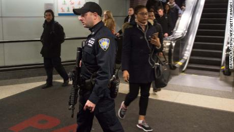 Port Authority Police watch as people evacuate after a reported explosion at the Port Authority Bus Terminal on December 11, 2017 in New York. 