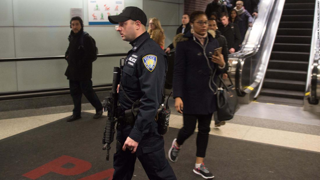Port Authority police watch as people evacuate after an explosion at the Port Authority bus terminal on Monday in New York.