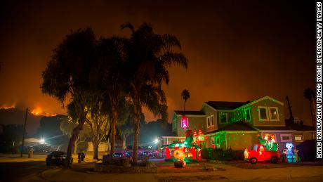 CARPINTERIA, CA - DECEMBER 10: Christmas decorations illuminate a house as the growing Thomas Fire advances toward Santa Barbara County seaside communities on December 10, 2017 in Carpinteria, California. The Thomas Fire has grown to 173,000 acres and destroyed at least 754 structures so far. Strong Santa Ana winds have been feeding major wildfires all week, destroying houses and forcing tens of thousands of people to evacuate.  (Photo by David McNew/Getty Images)