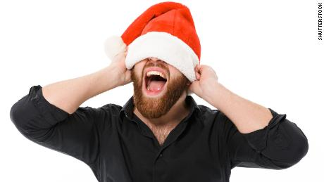 Screaming bearded man in shirt holding christmas hat on eyes over white background; Shutterstock ID 769720087; Job: -