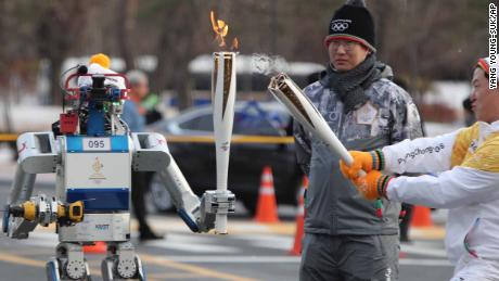 A DRC-Hubo robot holds an Olympic torch to be lit by bearer Dr. Dennis Hong, a professor at the University of California, Los Angeles, during the Olympic Torch Relay in Daejeon, South Korea, Monday, Dec. 11, 2017. The 2018 Pyeongchang Winter Olympics will be held from Feb. 9 to 25 in South Korea. (Yang Young-suk/Yonhap via AP)