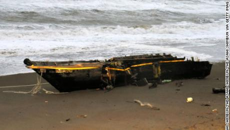 A wooden boat with Hangul character is washed ashore at a beach on December 12, 2017 in Kashiwazaki, Niigata, Japan. Two male bodies were found from the boat.  (Photo by The Asahi Shimbun via Getty Images)