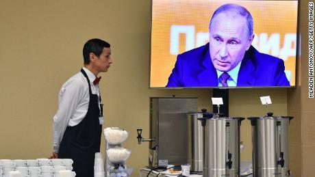 A waiter stands by a screen broadcasting Putin's marathon annual press conference in Moscow on Thursday.