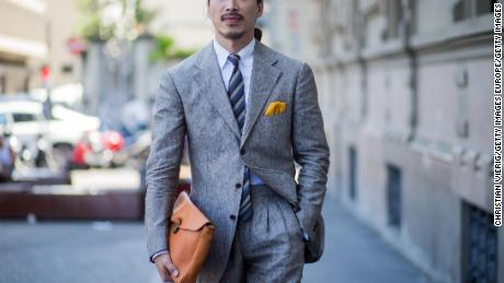 A guest wearing a grey suit and clutch is seen during Pitti Immagine Uomo 92 (2017)